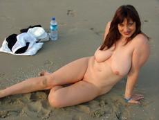 Busty MILF in dark stockings posing naked,..
