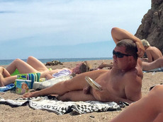 An elderly nudist sunbathes and reads a book on..