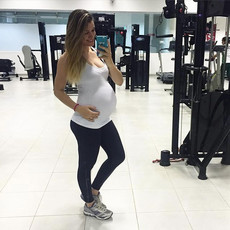 Pregnant young girl in a swimsuit gym selfie