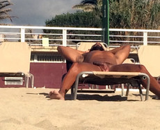 Tanned naked men sleeping on the beach